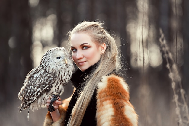Beautiful woman in a fur coat with an owl on his arm. blonde with long hair in nature