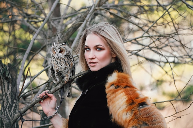 Beautiful woman in a fur coat with an owl on his arm.
