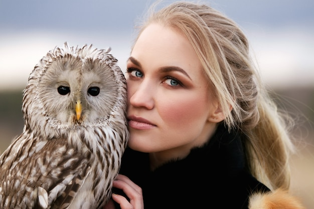 Beautiful woman in fur coat with an owl on his arm