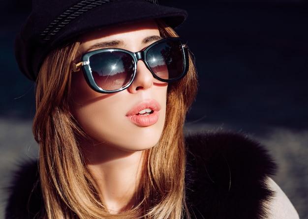 Beautiful woman in fur, urban style accessories and sunglasses. lynx fur fashion beauty. model