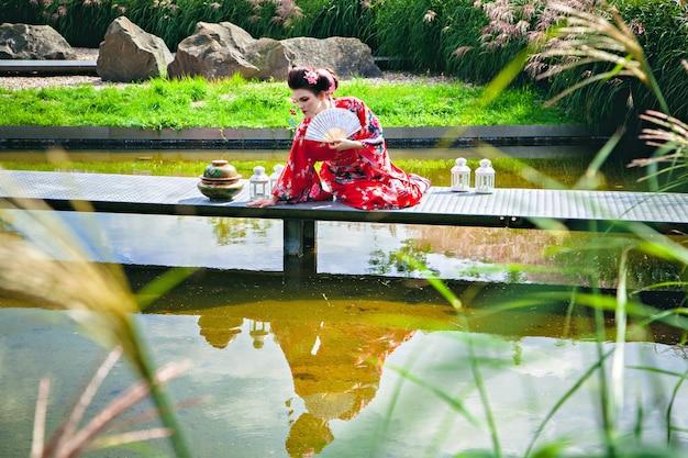 Beautiful woman in geisha costume in the garden on the bridge