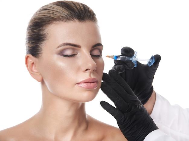 美しい女性は白い背景で隔離の彼女の顔に注射を取得します
