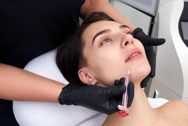 美しい女性は彼女の唇に注射を受けます