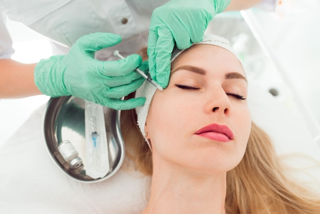 Красивая женщина получает инъекцию ботокса в ее лицо