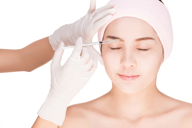 Beautiful woman gets an injection in her face,isolated on white with clipping path.