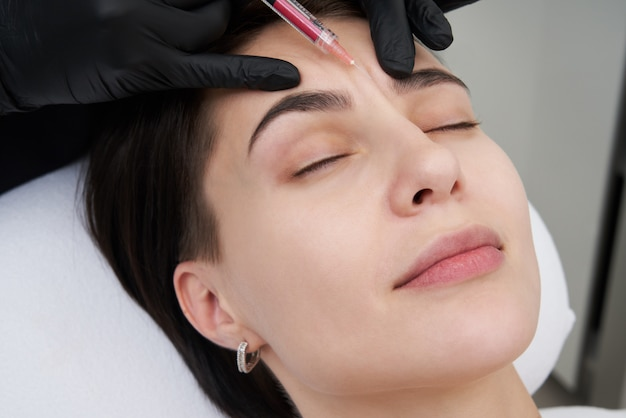 Beautiful woman gets an injection in her forehead