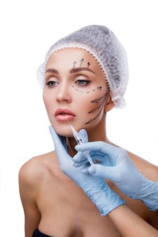 Beautiful woman gets injections cosmetology beauty face medical disposable cap markings on the face