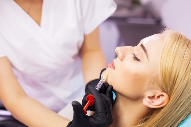 Beautiful woman getting beauty injection for lips