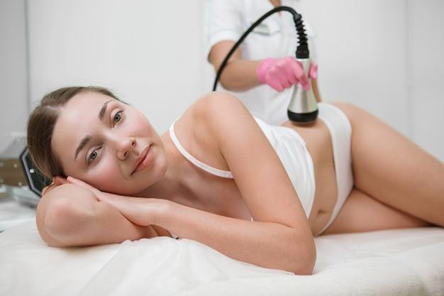 뷰티 클리닉에서 셀룰 라이트 감소 하드웨어 미용 치료를 받고 아름다운 여자