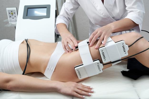 Красивая женщина, получающая электростимуляционную терапию, лазерное липо оборудование, косметическое уменьшение жира