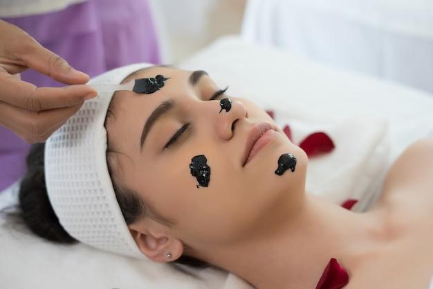 Красивая женщина получает лицевой черной маске грязи в салоне красоты.