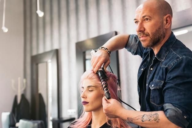 美容院で美容師に散髪されている美女。