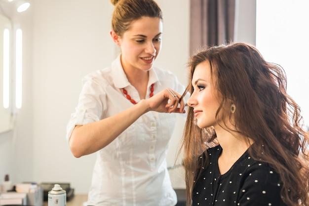 Красивая женщина стрижка парикмахером в салоне красоты