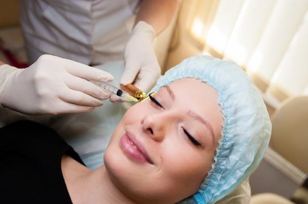Красивая женщина, получая подъемную инъекцию в скулы. инъекции омоложения кожи. косметические процедуры, инъекции.