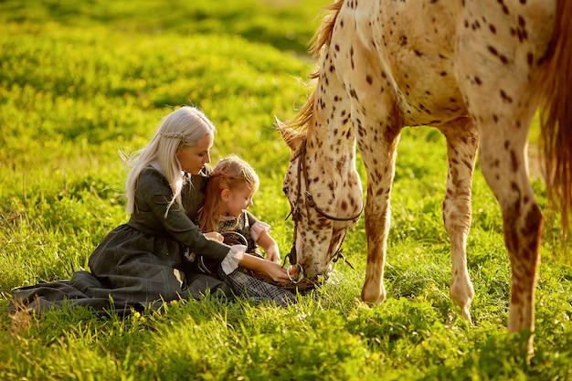 Beautiful woman and girl embracing horse