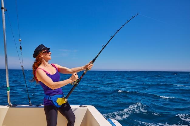 Beautiful woman girl fishing rod trolling in boat