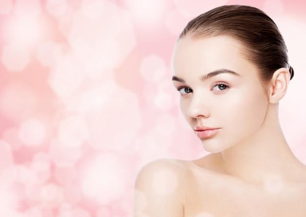 ピンクのボケ味の背景に美しい女性の女の子のナチュラルメイクスパスキンケアの肖像画