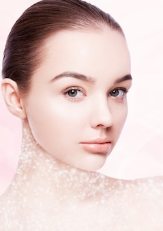 Beautiful woman girl natural makeup spa skin care portrait on pink bokeh background with glitter neck