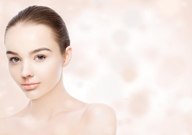 Beautiful woman girl natural makeup spa skin care portrait on pink bokeh background
