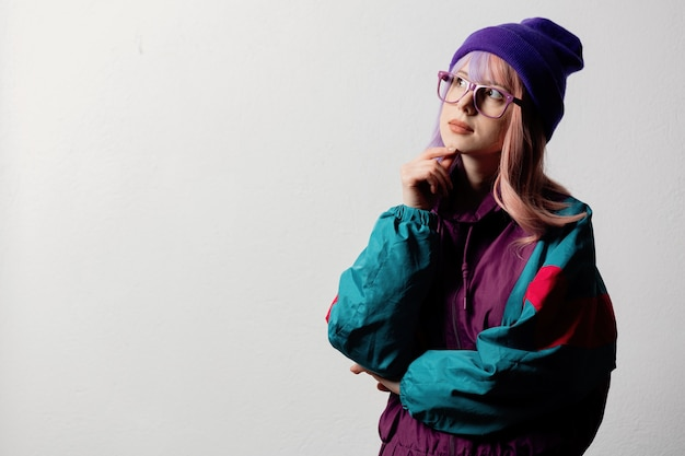 Beautiful woman in glasses and 80s sportsuit on white background