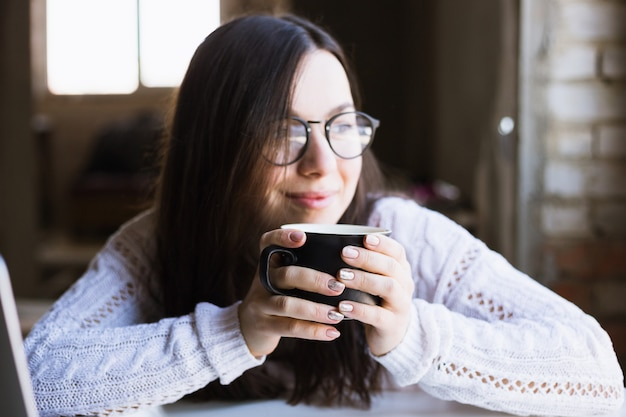 Beautiful woman in glasses sits holding a cup of coffee and using a laptop computer