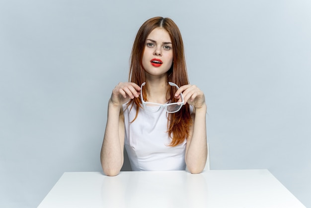 Beautiful woman in glasses sits at a table, light space, posing emotions