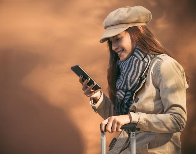 秋に旅行に行くと彼女の電話を使用して美しい女性