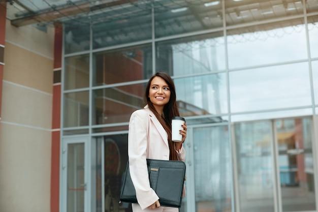 Красивая женщина собирается работать с кофе, гуляя возле офисного здания