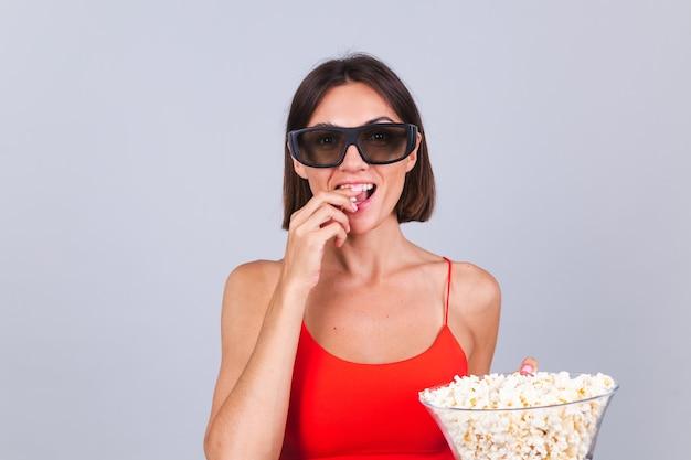 Bella donna sulla parete grigia in occhiali da cinema 3d con popcorn, allegre emozioni positive felici