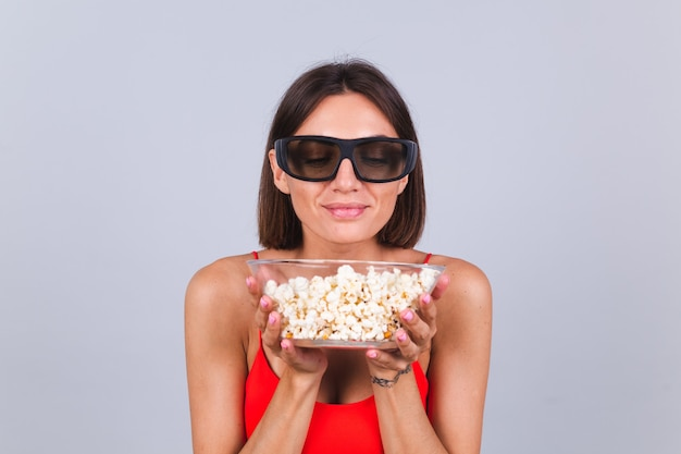 Beautiful woman on gray wall in 3d cinema glasses with popcorn, cheerful happy positive emotions