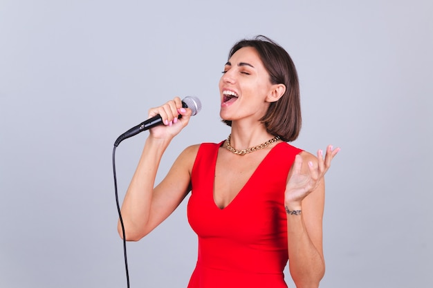 Beautiful woman on gray wall with microphone singing emotional favorite song happy positive cheerful