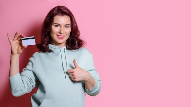 Beautiful woman in a green hoodie holds a bank card in her hands, smiles and looks at the camera. horizontal studio shot on pink background, copy space