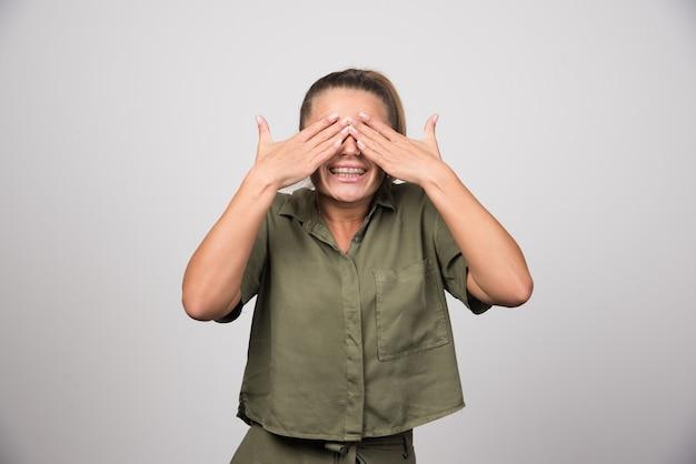 Bella donna in camicia verde che le copre gli occhi.