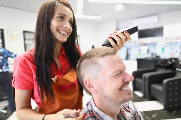 サロンの美女美容師が男性にスタイリッシュなヘアスタイルを演出します。クライアントに微笑んでいるマスター美容師