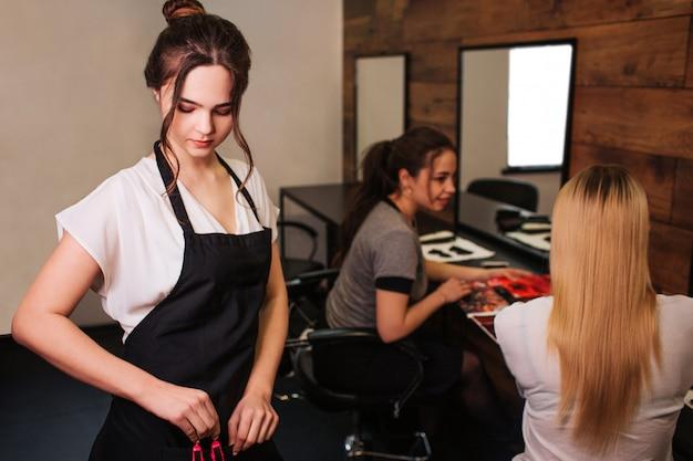 Красивый парикмахер женщины с черным передником принимая зажим профессионала волос перед парикмахерским искусством на салоне. красота и люди