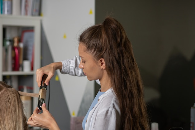 Парикмахер красивой женщины работая с белокурой женщиной в салоне волос. создание красивых локонов плойкой