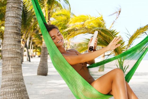 Beautiful woman in the hammock is applying sunscreen lotion.