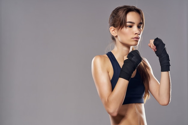 Beautiful woman hand bandages punch workout fighter dark background
