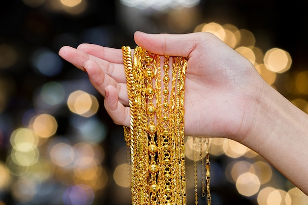 Beautiful woman hand hold gold necklace jewelry, accessory and fashion.