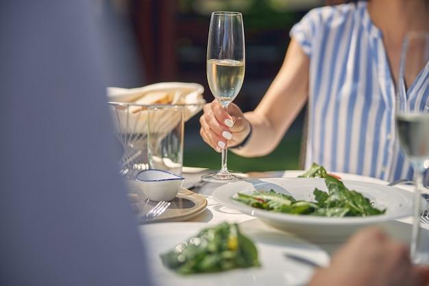 식탁에 앉아있는 동안 차가운 와인 잔을 들고 아름 다운 여자 손