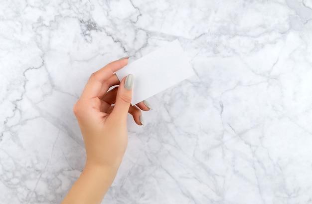 名刺を保持しているマニキュアを持つ美しい女性の手。