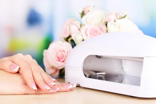 Красивая женщина руки и лампа для ногтей на столе на ярком фоне