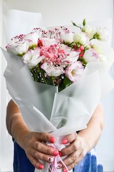 美しい女性の手は白い背景に白と紫の花の花束を保持します。無人。顔のない