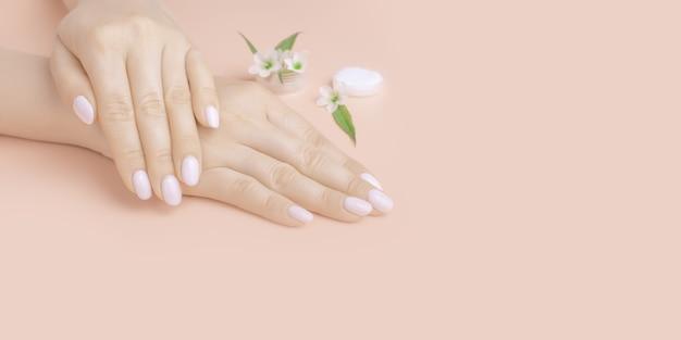 ピンクの背景に花と美しい女性の手。コンセプトハンドケア、アンチシワ、アンチエイジングクリーム、コスメティック