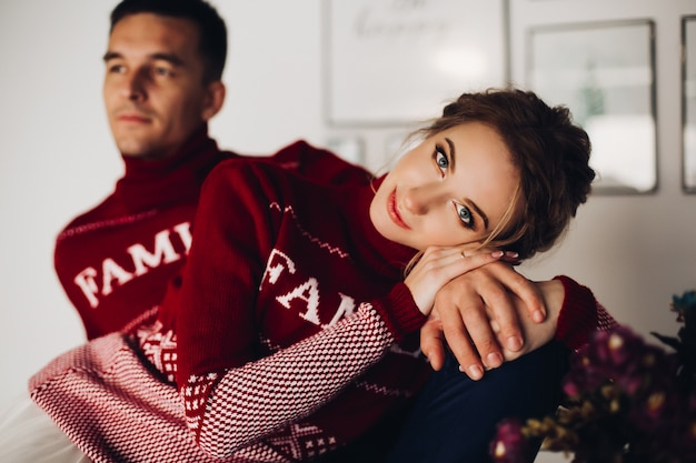 Beautiful woman and handsome boyfriend posing in red sweaterss