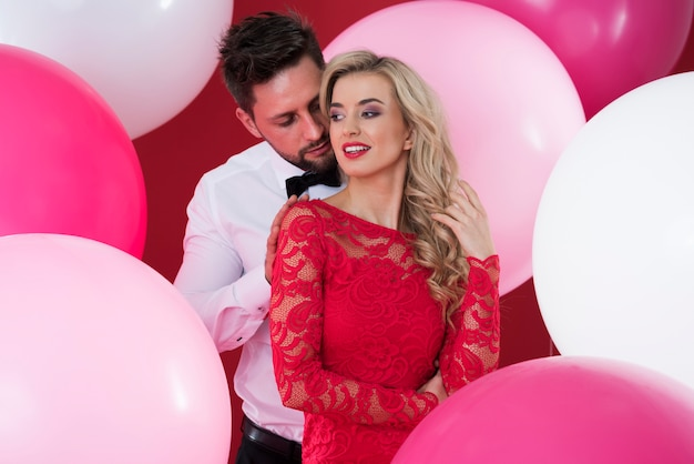 Beautiful woman and handsome man among the balloons