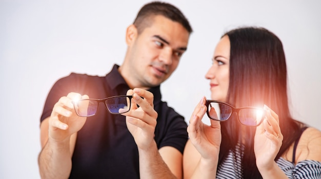 Beautiful woman and handsome man are holding eyeglasses in hands. white background. close up