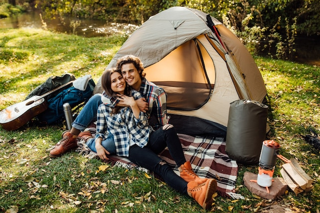 Beautiful woman and handsome man spending time on nature, sitting near the tent on the plaid