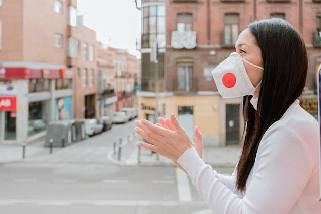 保護マスクを身に着けているとバルコニーで拍手美しい女性の幸せそうな顔