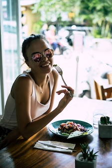 A beautiful woman has breakfast in a stylish cafe